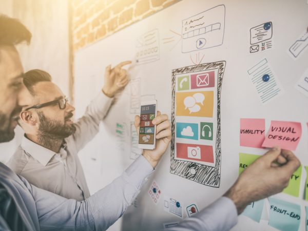 men designing a website using drawing and notes on a whiteboard, website design concept
